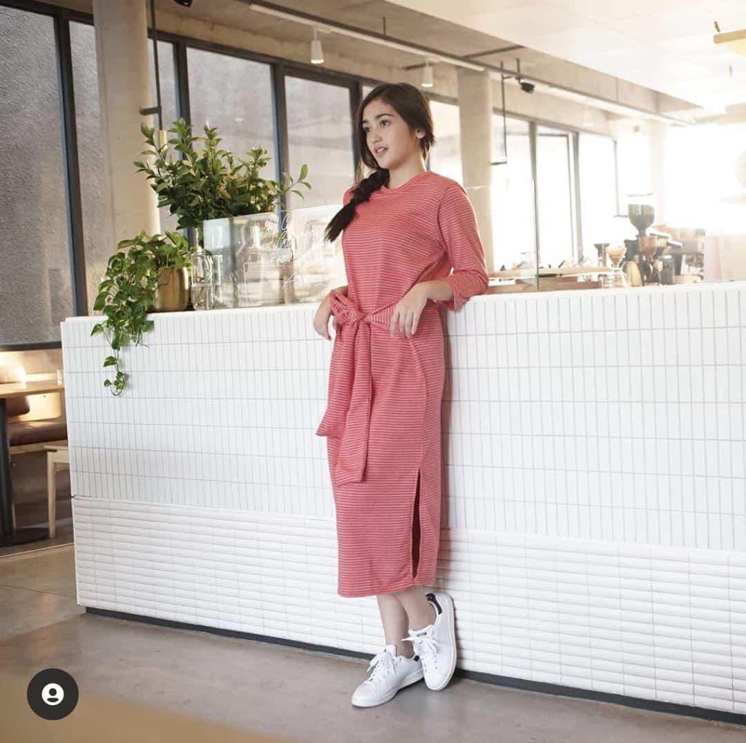 gaya casual Ranty Maria saat mengenakan gaun casual merah geris-garis dan sepatu sneakers